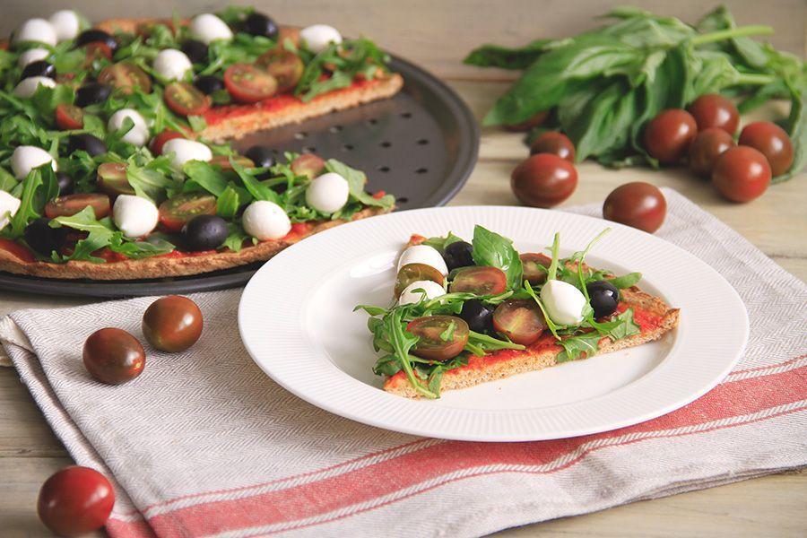Pizza integral con tomates cherry, rúcula y mozzarella fresca